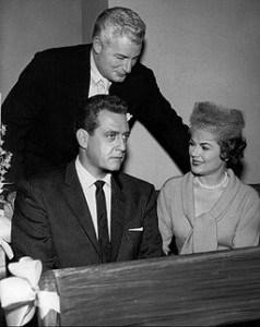 File: Photo of William Hopper (Paul Drake-standing), Raymond Burr (Perry Mason) and Barbara Hale (Della Street).  By CBS Television (eBay item photo front photo back) [Public domain], via Wikimedia Commons