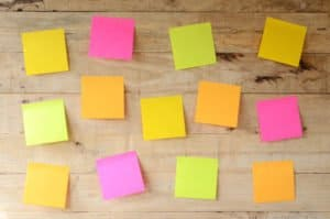 My blog post on Sticky Notes Letter Writing - image of empty colorful sticky notes on wooden bulletin board, ready for message
